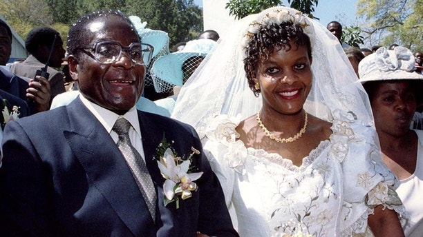 President Robert Mugabe and new wife Grace leave the Kutama Catholic Church August 17, 1996 after exchaning their wedding vows. The couple were traditionally married shortly after the death of Mugabe's first wife Sally. The ceremony was attended by six thousand invited guests.  REUTERS/Howard Burditt - PBEAHUMWKBR