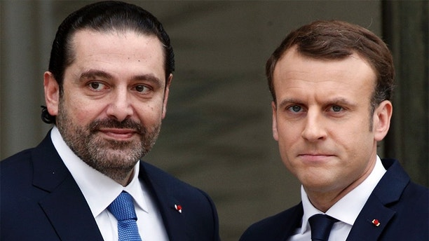 French President Emmanuel Macron, right, poses for photographers with Lebanon's Prime Minister Saad Hariri prior to their meetingl at the Elysee Palace in Paris, Saturday, Nov. 18, 2017. Hariri arrived in France on Saturday from Saudi Arabia and may be back in Beirut next week, seeking to dispel fears that he had been held against his will and forced to resign by Saudi authorities.(AP Photo/Thibault Camus)
