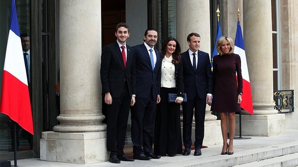 French President Emmanuel Macron, center right, and his wife Brigitte, right, greet Lebanon's Prime Minister Saad Hariri, second left, his wife Lara, center left and their son Hussam upon their arrival at the Elysee Palace in Paris, Saturday, Nov. 18, 2017. Hariri arrived in France on Saturday from Saudi Arabia and may be back in Beirut next week, seeking to dispel fears that he had been held against his will and forced to resign by Saudi authorities.(AP Photo/Christophe Ena)