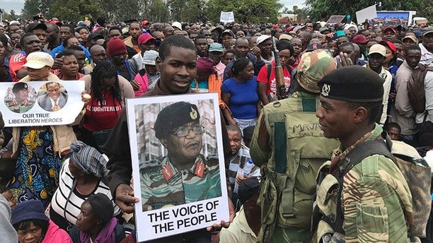 People gather to demonstrate for the ouster of 93-year-old President Robert Mugabe who is virtually powerless and deserted by most of his allies, in Harare, Zimbabwe, Saturday, Nov. 18, 2017. Zimbabwe's generals, including Constantino Chiwenga, on poster, have placed Mugabe under house arrest and have allowed him limited movement while talks on his exit from office unfold. (AP Photo/Ben Curtis)