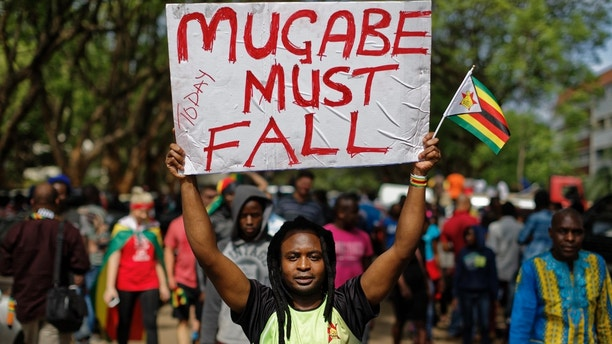 Protesters demanding President Robert Mugabe stands down march towards State House in Harare, Zimbabwe Saturday, Nov. 18, 2017. In a euphoric gathering that just days ago would have drawn a police crackdown, crowds marched through Zimbabwe's capital on Saturday to demand the departure of President Robert Mugabe, one of Africa's last remaining liberation leaders, after nearly four decades in power. (AP Photo/Ben Curtis)