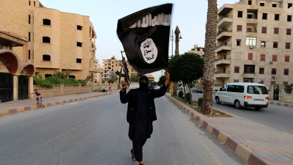 A member of the Islamic State waves an ISIS flag in Raqqa on June 29, 2014. Since then, ISIS has lost a large amount of territory in Syria and Iraq.