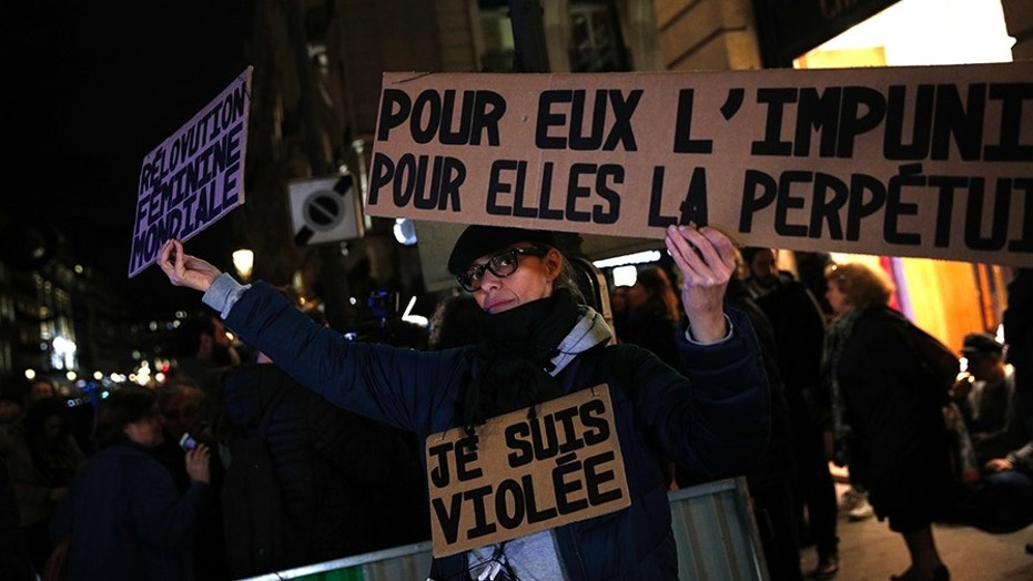 "An activist holds a banner reading: ""For him impunity, for her a life sentence,"" during a protest in Paris. Activists have protested demanding that the age of consent be set at 15."