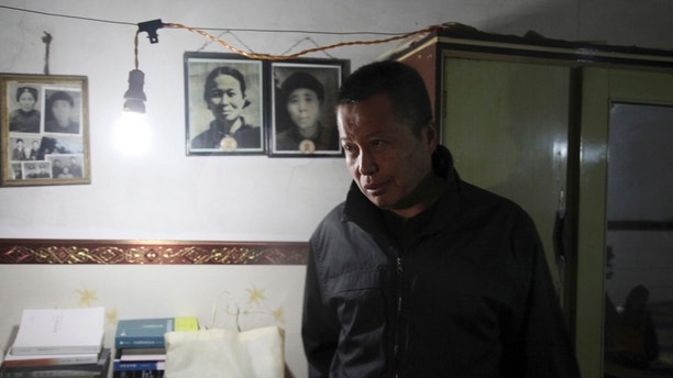 FILE - In this 2015, file photo, Gao Zhisheng walks past photos of his relatives in a cave home where he is confined in northwestern China's Shaanxi province. Gao's whereabouts are now unknown after a short lived escape from his state security captors. Gao's plight shows what activists say is a drastically deteriorating situation for rights campaigners under the rule of President Xi Jinping, who emerged from a party congress last month as the most powerful Chinese leader in a generation. (AP Photo/Paul Traynor, File)