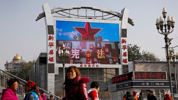 In this Thursday, Nov. 16, 2017, photo, people walk underneath a TV screen near a police kiosk showing a documentary footage of China's laws under five years of leadership by Chinese President Xi Jinping, at the Beijing railway station in Beijing. Activists are describing a drastic deterioration in China's treatment of human rights campaigners as the country's most powerful leader in a generation associates China's rise as a global power with highly authoritarian, one-party rule. (AP Photo/Andy Wong)