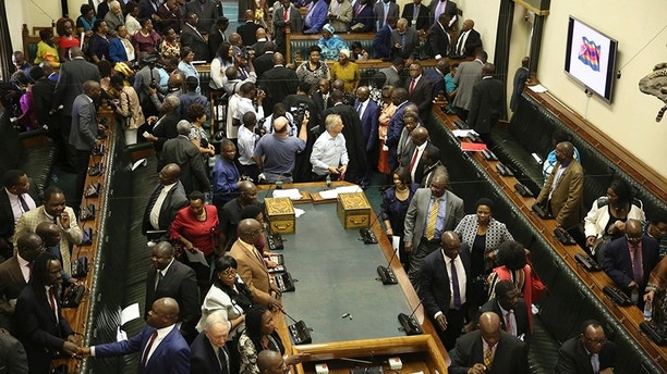 Members of the House of Assembly sit inside the Zimbabwean Parliament in Harare, Zimbabwe, Tuesday, Nov. 21 2017.  Parliament convened as the ruling party seeks to impeach President Robert Mugabe after nearly four decades in power. (AP Photo/Aaron Ufumeli)