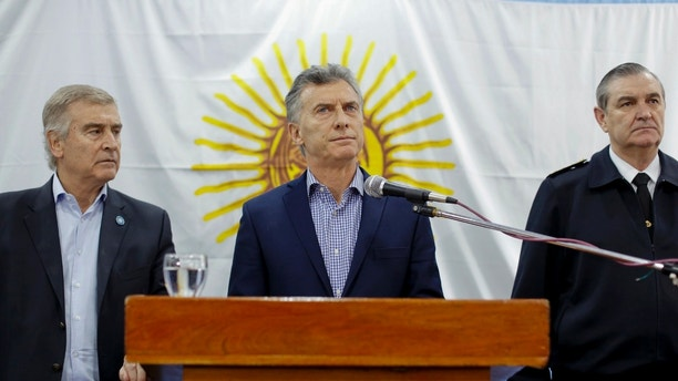 Argentine President Mauricio Macri, pauses as he gives a statement, flanked by Defense Minister Oscar Aguad, left, and Chief of the General Staff of the Navy Marcelo Eduardo Hipolito Srur at the navy headquarters in Buenos Aires, Argentina, Friday, Nov. 24, 2017. Macri said the international search for a submarine carrying 44 crew members that has been lost in the South Atlantic since Nov. 15 will continue and that the sub's disappearance will be investigated. (AP Photo/Victor R. Caivano)