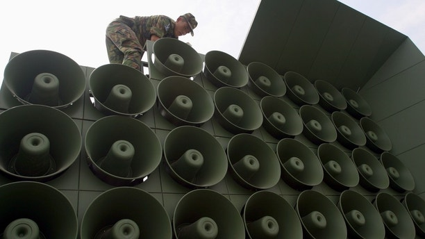 A SOUTH KOREAN SOLDIER WORKS TO REMOVE LOUDSPEAKERS SET UP FOR PROPAGANDA PURPOSES NEAR THE DEMILTARIZED ZONE IN PAJU. A South Korean soldier works to remove loudspeakers set up for propaganda purposes near the demiltarized zone in Paju, about 55km (34 miles) north of Seoul June 16, 2004. North and South Korea stopped blaring propaganda at each other across the fortified demilitarised zone border on Tuesday to mark the fourth anniversary of a landmark summit between their leaders. REUTERS/You Sung-Ho - RP5DRIBVLFAA