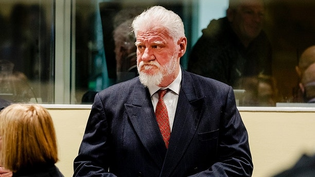 Slobodan Praljak, center, enters the Yugoslav War Crimes Tribunal in The Hague, Netherlands, Wednesday, Nov. 29, 2017, to hear the verdict in the appeals case. The hearing was suspended after Praljak claimed to have drunk poison and shouted that he was not a war criminal, after his 20-year sentence was upheld. A United Nations war crimes tribunal handed down its last judgment, in an appeal by six Bosnian Croat political and military leaders who were convicted in 2013 of persecuting, expelling and murdering Muslims during Bosnia's war in the tribunal's last case. (Robin van Lonkhuijsen,Pool Photo via AP)