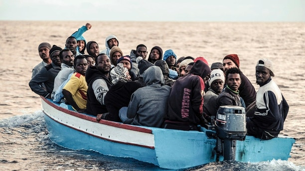 In this Nov. 22, 2017 photo provided Thursday, Nov. 23, 2017,  migrants on a small wooden boat wait to be rescued by the German non-profit organization Sea Watch, in the central Mediterranean Sea. According to the Italian Coast Guard, some 1100 migrants were rescued on Wednesday from the central Mediterranean Sea in different rescue operations by the Italian Coast Guard, the Italian Navy and several NGO's, including Sea Watch who has 254 people are on board their ship which is heading to Italy. (Johannes Moths/Sea Watch via AP)