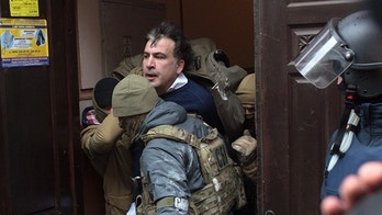 The Ukrainian Security Service officers detain Mikheil Saakashvili at the entrance of his house in Kiev, Ukraine, Tuesday, Dec. 5, 2017. Ukraine's intelligence agency on Tuesday detained the former president of Georgia who has emerged as an anti-corruption campaigner in his new country but faced an angry backlash of protesters who would not let the officers to take him away. (AP Photo/Evgeniy Maloletka)