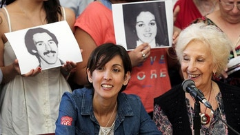 Estela de Carlotto (R), president of human rights organization Abuelas de Plaza de Mayo (Grandmothers of Plaza de Mayo), smiles next to Adriana (she wished not to release her current last name), who was taken away from her mother during the 1976-1983 Argentinian dictatorship, at a news conference in Buenos Aires, Argentina December 5, 2017. People in the back hold portraits of Adriana's parents Graciela Ortolani and Edgardo Garnier. REUTERS/Bernardino Avila - RC16358630C0