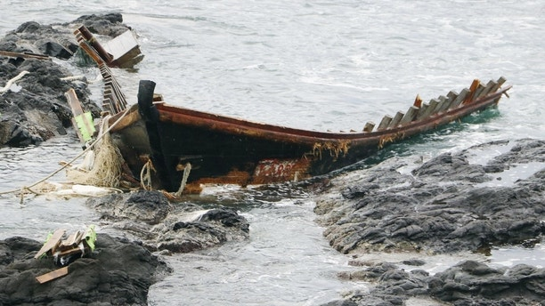 "A wooden boat is left after being dragged ashore in Tsuruoka, Yamagata prefecture, northern Japan on Monday, December 4, 2017. The coast guard said that a Japanese fishing boat picked up a body of a man that floated off the coast of Sakata in the prefecture and two more bodies were thrown onto a nearby beach an hour and a half later. Twenty-eight of the ships, dubbed ""ghost ships,"" were detected in November, compared to only four in November last year. (Kyodo News via AP)"