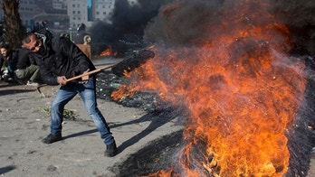 A Palestinian protester burns tires during clashes with Israeli troops following protests against U.S. President Donald Trump's decision to recognize Jerusalem as the capital of Israel, in the West Bank city of Ramallah, Thursday, Dec. 7, 2017. (AP Photo/Nasser Nasser)