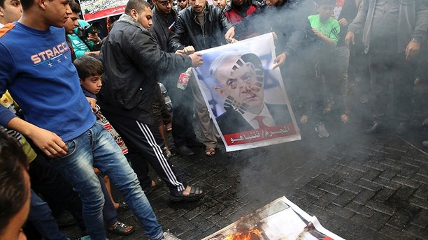 Hamas supporters burn a picture of the Israeli Prime Minister Benjamin Netanyahu during protest against U.S. President Donald Trump's decision to recognize Jerusalem as Israel's capital, in Jebaliya Refugee Camp, Gaza Strip, Friday, Dec. 8, 2017. (AP Photo/Adel Hana)