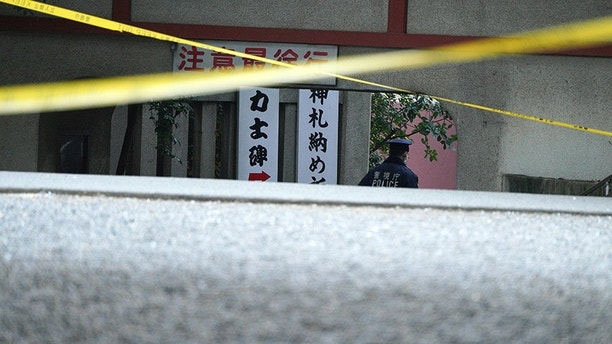 A police officer walks near the scene of a stabbing attack at Tomioka Hachimangu shrine in Tokyo Friday, Dec. 8, 2017. Police say three people have died in the stabbing attack on Thursday night at the prominent shrine, including the head priest and the attacker, who apparently took his own life. (AP Photo/Eugene Hoshiko)