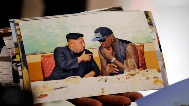 Former basketball star Dennis Rodman of the U.S. shows a picture which he took with North Korean leader Kim Jong-un as he arrives at Beijing Capital International Airport September 7, 2013. Kim again met Rodman during his second visit to North Korea this year, North Korea's state news agency said on Saturday but made no mention on whether the two discussed the fate of a jailed American missionary. 