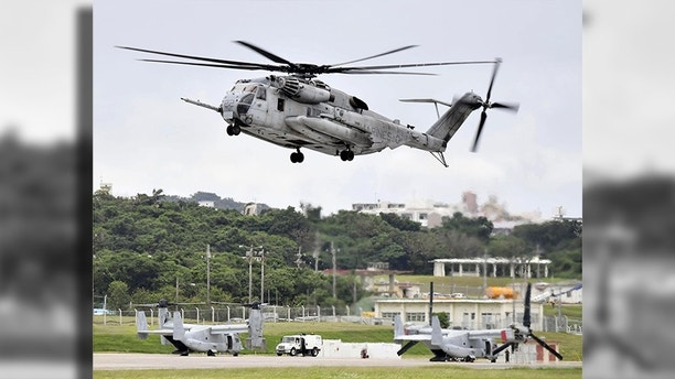 This Oct. 2017 photo shows U.S. Forces' CH53E helicopter in Ginowan, Okinawa. A metal window frame has fallen from a U.S. military aircraft in flight and landed on a school playground on Okinawa, leaving a boy with minor injury from small gravels stirred up from the ground and escalating anti-American base sentiment on the southern island. (Ryosuke Uematsu/Kyodo News via AP)