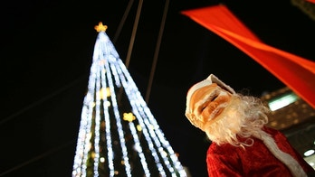 A boy wearing a Santa Claus costume attends a Christmas tree lighting ceremony in the northern town of Nazareth, the town of Jesus' boyhood, December 12, 2012. REUTERS/Ammar Awad (ISRAEL - Tags: RELIGION) - GM1E8CD0CSI01