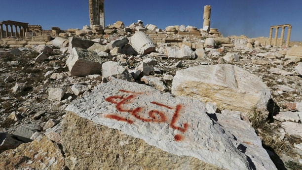 "Graffiti sprayed by Islamic State militants which reads ""We remain"" is seen on a stone at the Temple of Bel in the historic city of Palmyra, in Homs Governorate, Syria April 1, 2016. REUTERS/Omar Sanadiki  SEARCH ""PALMYRA SANADIKI"" FOR THIS STORY. SEARCH ""THE WIDER IMAGE"" FOR ALL STORIES - GF10000368444"
