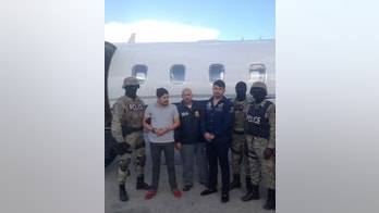 Efrain Antonio Campo Flores (2nd from L) and Franqui Francisco Flores de Freitas stand with law enforcement officers in this November 12, 2015 photo after their arrest in Port Au Prince, Haiti.    Courtesy of U.S. Attorney's Office Manhattan/Handout via REUTERS      ATTENTION EDITORS - THIS IMAGE WAS PROVIDED BY A THIRD PARTY. EDITORIAL USE ONLY - TM3ECB30ZVB01