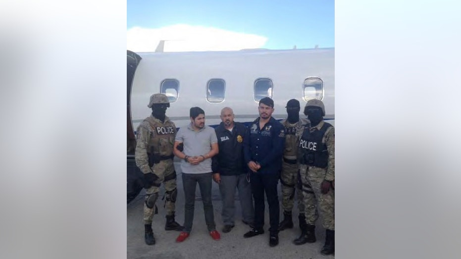 Efrain Antonio Campo Flores (2nd from L) and Franqui Francisco Flores de Freitas stand with law enforcement officers in this November 12, 2015 photo after their arrest in Port Au Prince, Haiti.
