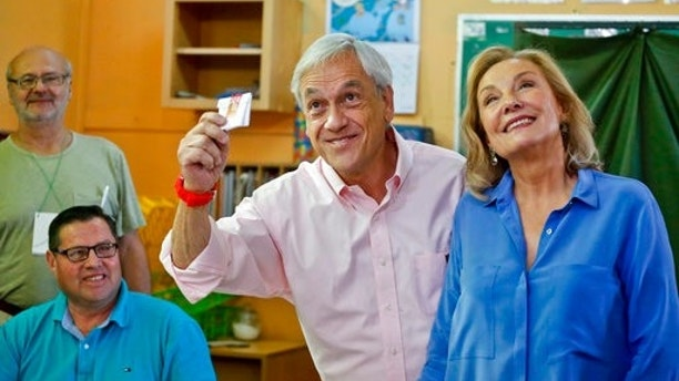 Former Chilean President and current presidential candidate Sebastian Pinera show his vote accompained with his wife Cecilia Morel during presidential elections runoff in Santiago, Chile, Sunday, Dec. 17, 2017. Chileans voters will decide Sunday whether to swing the world's top copper-producing country to the right or maintain its center-left path in a fiercely contested presidential runoff election. (AP Photo/Esteban Felix)