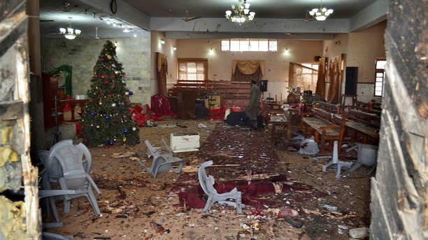 A Pakistani walks in the main hall of a church following a suicide attack in Quetta, Pakistan, Sunday, Dec. 17, 2017. Two suicide bombers attacked the church when hundreds of worshippers were attending services at the church ahead of Christmas. (AP Photo/Arshad Butt)