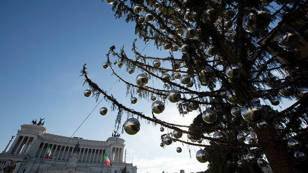 The Rome's official Christmas tree stands in front of the Unknown monument in Piazza Venezia Square. Despite the tree's 600 silver-colored decorative balls, the half-bare branches lend the square a forlorn rather than festive look and critics note that across town, the Vatican's Christmas tree, from Poland, looks healthy. (AP Photo/Alessandra Tarantino)