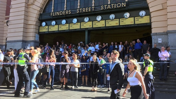 Members of the public stand behind police tape after Australian police said on Thursday they have arrested the driver of a vehicle that ploughed into pedestrians at a crowded intersection near the Flinders Street train station in central Melbourne, Australia December 21, 2017.  REUTERS/Melanie Burton - RC1F35C6E760