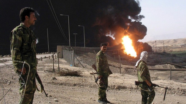 FILE - In this Oct. 12, 2005 file photo, Iraqi soldiers stand as an oil pipeline burns following an explosion in Beiji, Iraq. Iraq has invited bidders to express interest to build an oil pipeline that sends crude to international market through Turkey's Mediterranean port of Ceyhan. (AP Photo/Bassim Daham, File)