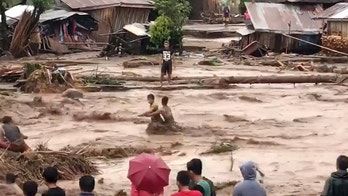 In this photo made from video by Aclimah Disumala, Friday, Dec. 22, 2017, villagers ross raging flood waters in Lanao del Norte, Zamboanga Pennisula, southern Philippines. A tropical storm has unleashed flash floods and set off landslides in the southern Philippines leaving dozens of people dead. (Aclimah Disumala via the AP)