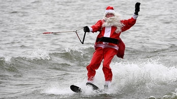 A man dressed as Santa Claus waterskis for an annual Christmas Eve performance on the Potomac River, Alexandria, Virginia, U.S. December 24, 2017.  REUTERS/Mike Theiler - RC133D63C8C0