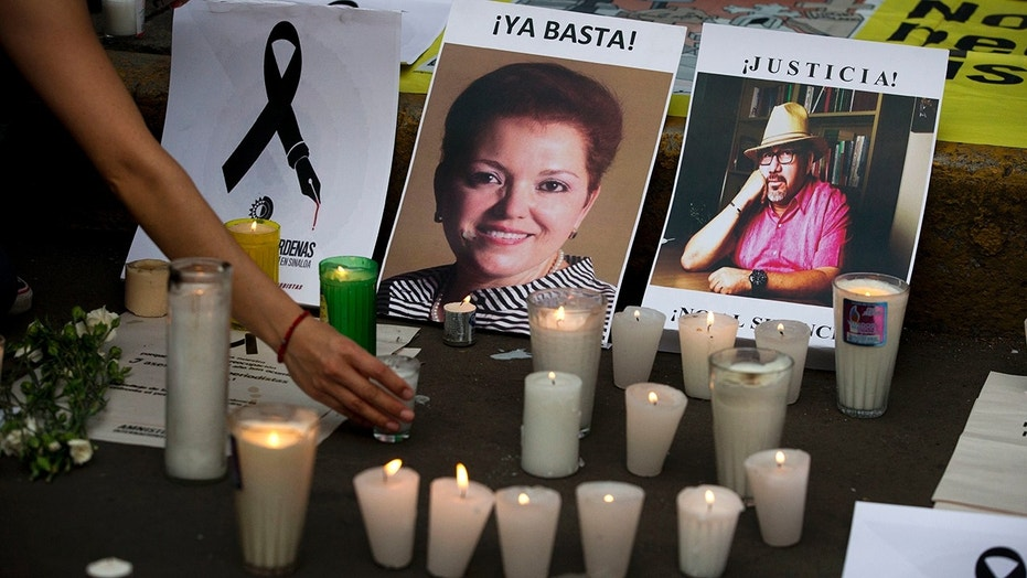 In this May 16, 2017, file photo, a woman places a candle in front of pictures of murdered journalists Miroslava Breach, left, and Javier Valdez during a demonstration against the killing of journalists, outside the Interior Ministry in Mexico City.