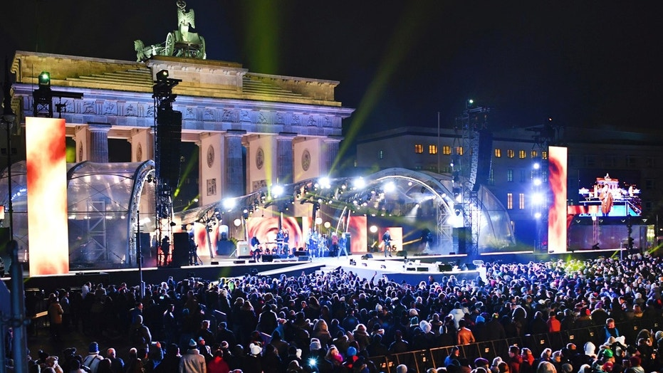In this Dec. 31, 2016 file photo numerous visitors stand in front of the stage at the Brandenburg Gate where the New Year's Eve party is taking place in Berlin, Germany.