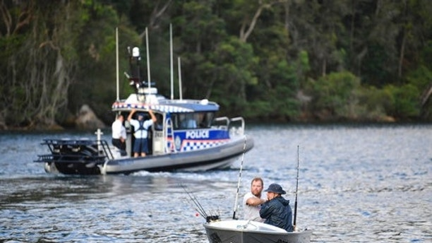 Fishermen guide their boat past a police vessel at the scene where a seaplane crashed into the Hawkesbury River, north of Sydney, Australia, Sunday, Dec. 31, 2017. The plane crashed into a river killing all six people on board, officials said. (Perry Duffin/AAP Image via AP)