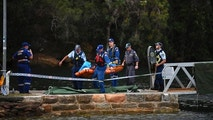 Emergency workers carry to shore what is believed to be a body and debris from a seaplane that crashed into the Hawkesbury River, north of Sydney, Australia, Sunday, Dec. 31, 2017. The plane crashed into a river killing all six people on board, officials said. (Perry Duffin/AAP Image via AP)