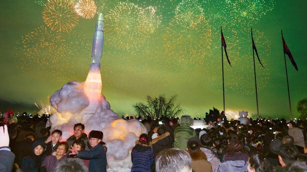 Fireworks are seen above the Taedong River during New Year celebrations as visitors pose for a photo in front of an ice sculpture of an intercontinental ballistic missile at the Pyongyang Ice Sculpture Festival in Kim Il Sung Square in Pyongyang, North Korea in this photo released by Kyodo January 1, 2018. Mandatory credit Kyodo/via REUTERS ATTENTION EDITORS - THIS IMAGE WAS PROVIDED BY A THIRD PARTY. MANDATORY CREDIT. JAPAN OUT. NO COMMERCIAL OR EDITORIAL SALES IN JAPAN.     TPX IMAGES OF THE DAY - RC1D65AE46F0