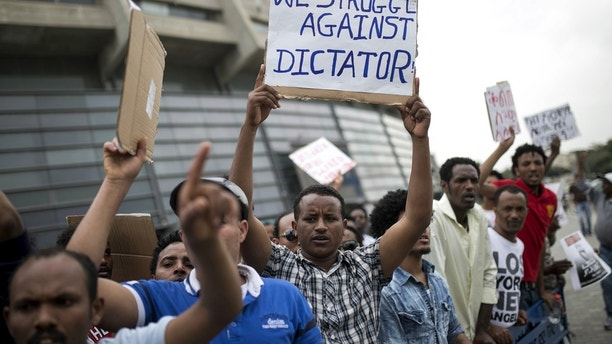 Eritrean refugees hold placards during a protest against the Eritrean government outside their embassy in Tel Aviv, Israel May 11, 2015. REUTERS/Baz Ratner  - GF10000091225