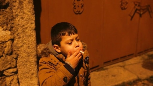 A young boy smokes in the street in the village of Vale de Salgueiro, northern Portugal, during the local Kings' Feast Friday, Jan. 5, 2018. The village's Epiphany celebrations, called Kings' Feast, feature a tradition that each year causes an outcry among outsiders: parents encourage their children, some as young as 5, to smoke cigarettes. (AP Photo/Armando Franca)