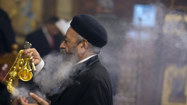 Coptic Orthodox priest, Pakhomios, spreads incense during Christmas Eve Mass at Virgin Mary church in Cairo, Egypt, late Saturday, Jan. 6, 2018. The Coptic Christian population are considered to be the largest Christian community in the Middle East and observe Christmas on January 7 according to the old, Julian calendar. (AP Photo/Amr Nabil)