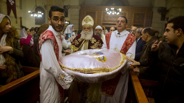 Coptic Orthodox priest, Tadros, center, carries communion bread during Christmas Eve Mass at Virgin Mary church in Cairo, Egypt, late Saturday, Jan. 6, 2018. The Coptic Christian population are considered to be the largest Christian community in the Middle East and observe Christmas on January 7 according to the old, Julian calendar. (AP Photo/Amr Nabil)