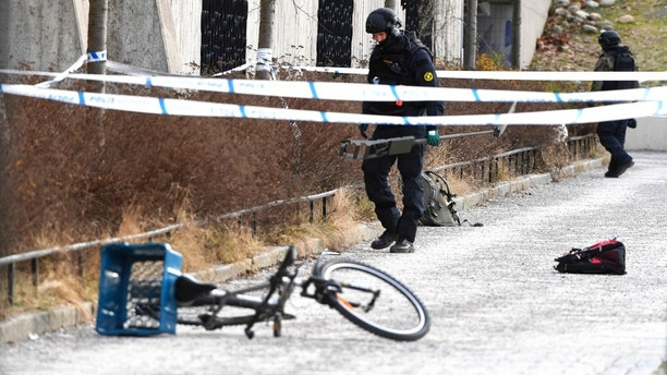 Swedish police search the area outside Varby Gard metro station, in Stockholm, near to where two people were injured by some kind of explosion, Sunday Jan. 7, 2018.  An unidentified explosive device is reported to have detonated Sunday, injuring at least two people.  (Henrik Montgomery / TT via AP)