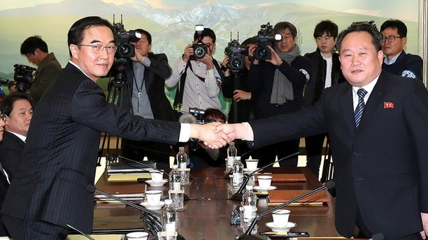 South Korean Unification Minister Cho Myoung-gyon, left, shakes hands with the head of North Korean delegation Ri Son Gwon before their meeting at the Panmunjom in the Demilitarized Zone in Paju, South Korea, Tuesday, Jan. 9, 2018. South Korean media said North and South Korea have begun talks at their border about how to cooperate in next month's Winter Olympics and how to improve their long-strained ties. (Korea Pool/Yonhap via AP)