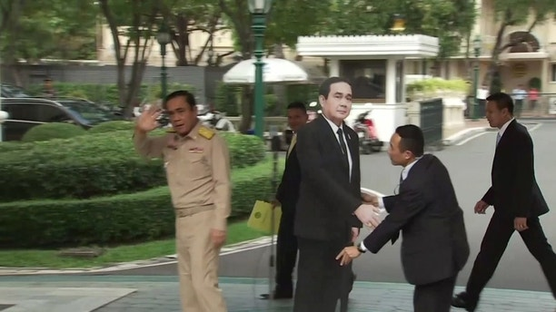 "In this image from video, Thailand's Prime Minister Prayuth Chan-ocha, left, waves and walks off as a life-sized cardboard cut-out figure of himself is placed next to the microphone during a media conference in Bangkok, Thailand, Monday Jan. 8, 2018.  Prayuth evaded questions by bringing out a life-sized cardboard cut-out of himself, and telling reporters to ""ask this guy"" if they had ""any questions on politics or conflict"" then turned on his heel and walked off, leaving the mock-up behind, to bemused looks and awkward laughter from the assembled media. (TPBS via AP)"