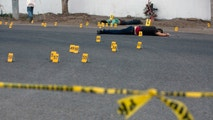 """FILE - In this June 29, 2017 file photo, investigators mark the spot where spent bullet casing fell next several bodies lying on a road in the town of Navolato, Sinaloa state, Mexico. Five states in Mexico have gotten the sternest """"do not travel"""" advisories under a revamped U.S. State Department system unveiled Wednesday, Jan. 10 2017. The five include the northern border state of Tamaulipas and the Pacific coast states of Sinaloa, Colima, Michoacan and Guerrero, placing the states on the same level warning level as Somalia, Yemen, Syria or Afghanistan. (AP Photo/Enric Marti, File)"""