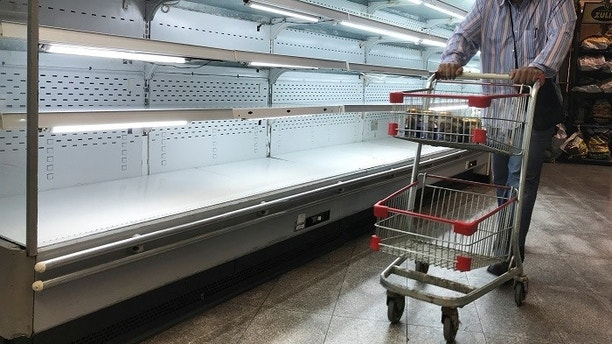 A man walks past an empty refrigerator at a supermarket in Caracas, Venezuela January 9, 2018. REUTERS/Marco Bello - RC11AC73F3B0
