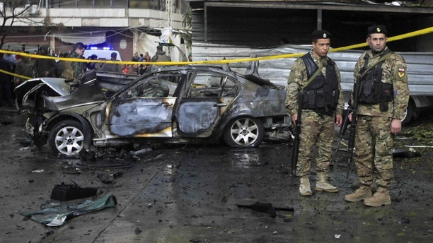 Lebanese army soldiers stand guard near a car that was destroyed in a bombing, in the southern port city of Sidon, Lebanon, Sunday, Jan 14, 2018. The Lebanese military said the bomb went off in a car in southern Lebanon, wounding its Palestinian owner. It was not immediately clear who carried out Sunday's bombing in the city of Sidon or why the Palestinian, identified as Mohammed Hamdan, was targeted. (AP Photo/Mohammed Zaatari)