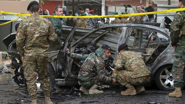 Lebanese army soldiers inspect a car that was destroyed in a bombing in the southern port city of Sidon Lebanon Sunday Jan 14 2018. The Lebanese military said the bomb went off in a car in southern Lebanon wounding its Palestinian owner. It was not