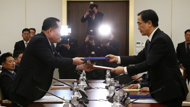 Head of the North Korean delegation, Ri Son Gwon exchanges documents with South Korean counterpart Cho Myoung-gyon after their meeting at the truce village of Panmunjom in the demilitarised zone separating the two Koreas, South Korea, January 9, 2018   REUTERS/Korea Pool -    RC14F637D290